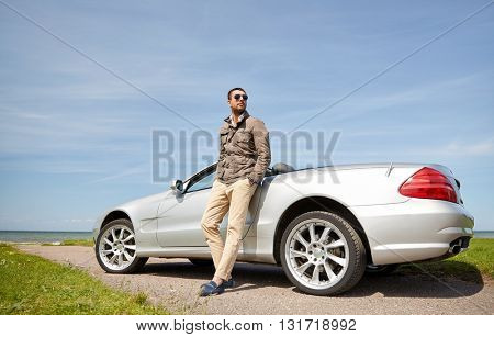 road trip, travel, transport, leisure and people concept - man near cabriolet car outdoors