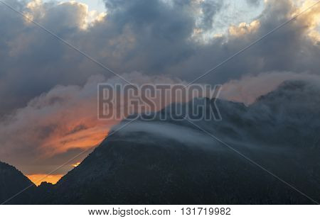 Beautiful sunset on the mountain under clouds