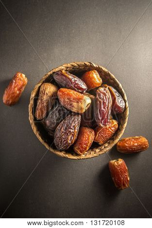 Sweet and ripen dates in basket. Most common and popular fruit in Arabian countries. Top view on dark background.