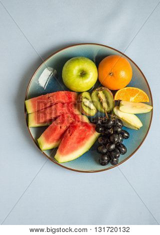 Healthy mix fruit platter. Slices of watermelon, oranges along with whole apple and bunch of grapes.