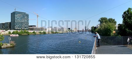 BERLIN, GERMANY - MAY 10, 2016: wealth and poverty in Berlin. A tramp on the River Spree looks at the Mercedes Benz Arena