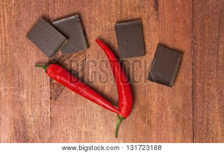 Two red hot chilli peppers with pieces of dark chocolate around them shot from above on a brown wooden texture with copyspace
