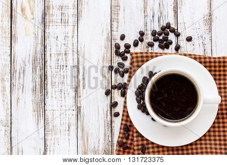 Coffee cup and coffee beans on white wooden table. top view