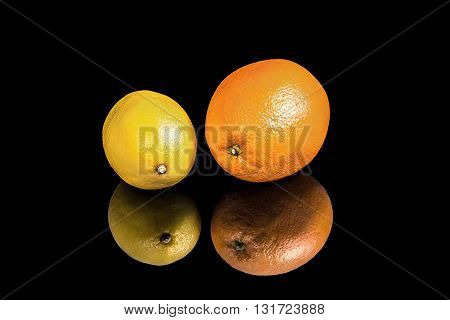 Juicy lemon and orange on black background