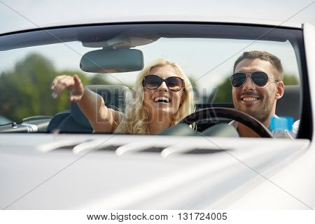 road trip, travel, couple and people concept - happy man and woman driving in cabriolet car outdoors