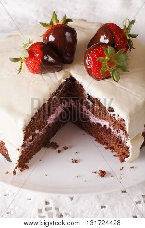 Beautiful Chocolate Cake With White Icing And Strawberries Close-up. Vertical