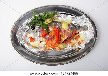 Whole baked dorado fish with vegetables on a tray