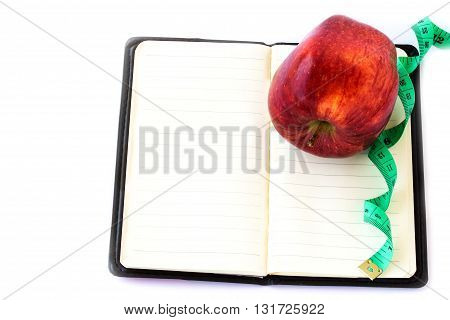 Red apple and measuring tape on notebook on a white background