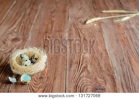 Brown wooden backgrond with nest with quail eggs and wheat ear