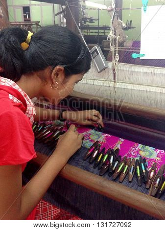 Mandalay Myanmar - April 21 2013 : Young Burmese women weaving cotton in a silk and cotton factory