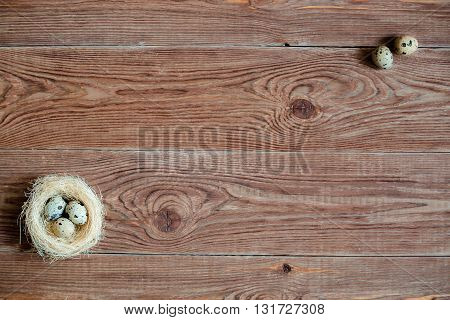 Brown wooden backgrond with nest with quail eggs in a corner