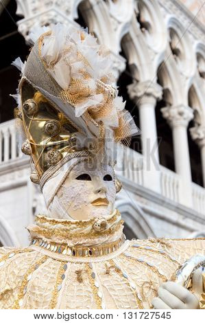 Venice, Italy - February 15, 2015: An unidentified person on a traditional vennetian carnival costume in front of the Doges Palace during the Carnival of Venice in Italy.