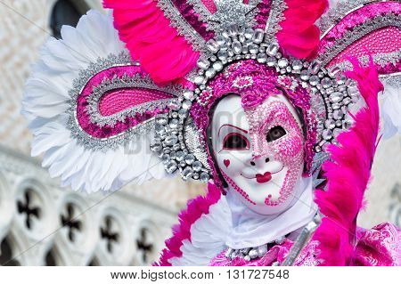 Venice, Italy - February 15, 2015: A model disguised with a white and pink costume in front of the Doges Palace during Venice carnival.