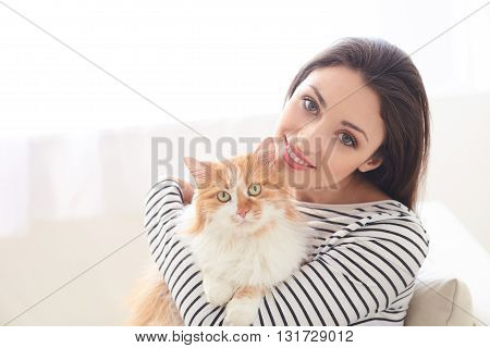Beautiful girl is relaxing at home with her lovely cat. She is sitting and embracing her pet. The lady is smiling and looking forward with happiness