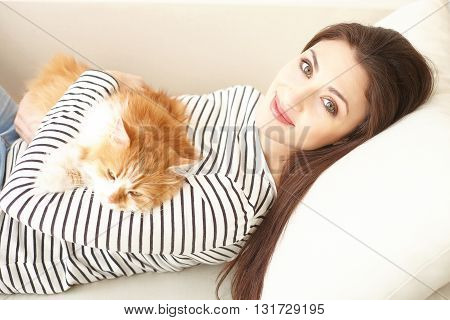 Cheerful woman is lying on sofa and embracing her cat. She is looking at camera and smiling happily