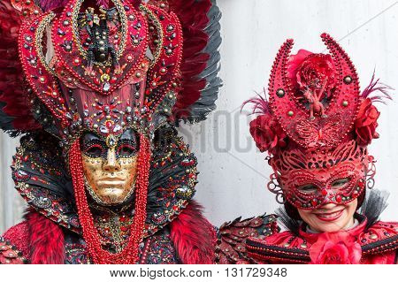Venice, Italy - February 15, 2015: Woman smiling in a red venetian carnival costume next an unidentified person on a similar costume at the Carnival of Venice in Italy.