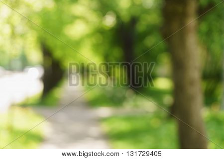 blurred background of sidewalk in town in bright sunne summer day, natural bokeh high resolution