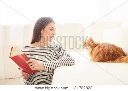 Beautiful young woman is reading to the cat. She is sitting and holding a book. The lady is smiling. Animal is lying on sofa and looking at her with interest