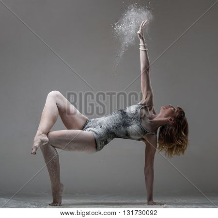 Beautiful expressive ballet dancer posing with flour at studio on gray