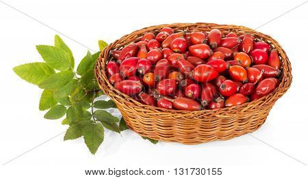 Rosehip berries in a wicker basket isolated on white background.