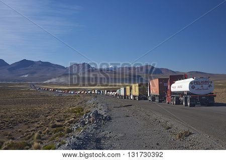 LAUCA NATIONAL PARK, CHILE - MAY 11, 2016: Long line of trucks waiting on the altiplano of northern Chile to cross into Bolivia.