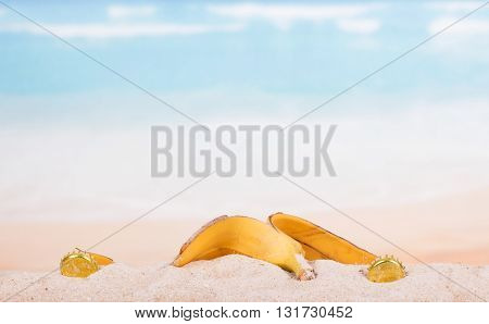 Banana peel and plug in the sand against the sea.