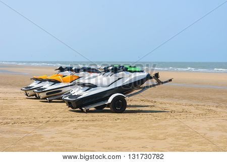 jet ski boats parked on trailers on the beach