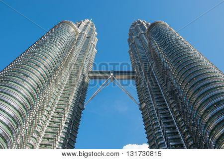 KUALA LUMPUR MALAYSIA - FEBRUARY 29: Bottom view of Petronas twin towers on February 29 2016 in Kuala Lumpur Malaysia. The famous skyscraper with blue sky.