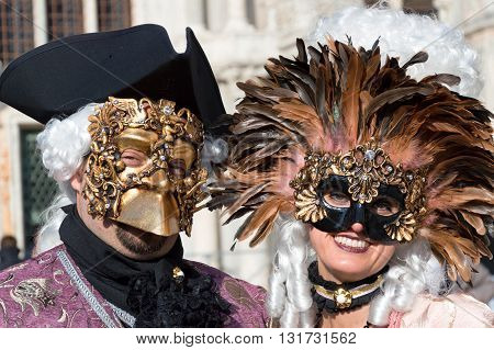 Venice, Italy - February 15, 2015: Two unidentified persons on traditional venetian costumes smiling during the Carnival in Venice