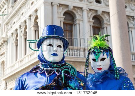 Venice, Italy - February 15, 2015: Two models disguised with similar blue carnival costumes, posing in San Marco square during the Carnival of Venice.