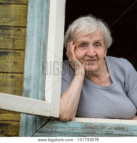 Portrait of a Slavic grandmother looking out the window of his house.