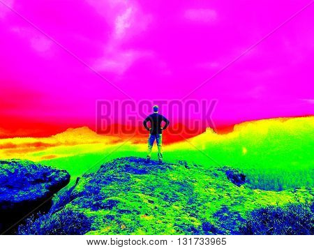 Fantastic infrared scan. Tired tourist in on mountain. Wonderful daybreak in mountains, heavy mist in deep valley