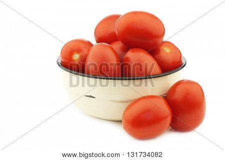 fresh and colorful italian roma tomatoes in an enamel bowl on a white background