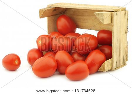 fresh and colorful italian roma tomatoes in a wooden crate on a white background