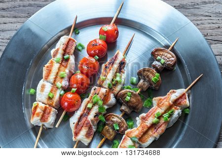 Grilled chicken and vegetable skewers on the metal plate