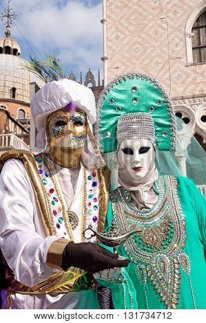 Venice, Italy - February 15, 2015: Two models disguised with traditional venetian costumes, posing with an aladdin lamp during the Carnival of Venice, in Italy.