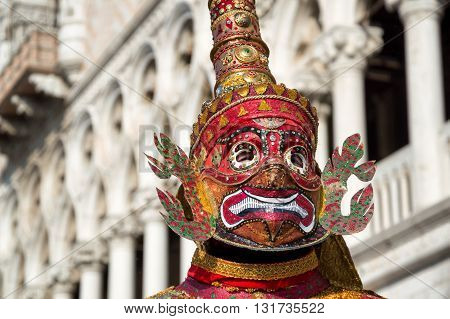 Venice, Italy - February 15, 2015: An unidentified person on a oriental style mask posing posing in front of the Doges Palace during the Carnival of Venice, in Italy.