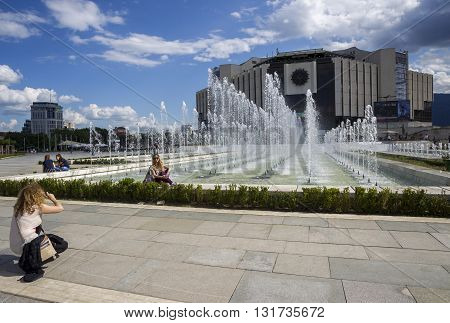 SOFIA BULGARIA - MAY 27: Women photographed in front of National Palace of Culture which is the largest multifunctional congress conference convention and exhibition centre in Southeastern Europe in Sofia Bulgaria on May 27 2016.