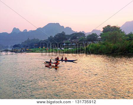 Recreation.Tourist kakaking and tubing along the river Nam Song at sunrise. Vang Vieng Laos.