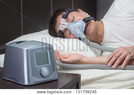 Asian man with sleep apnea using CPAP machine wearing headgear mask connecting to air tube