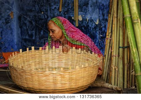 Jodhpur - AUGUST 23: An indian woman in colorful sari braiding a basket at traditional handicraft bazaar in Jodhpur on August 23 2013 in Jodhpur India