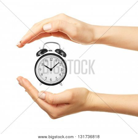 Female hands holding a clock isolated on white