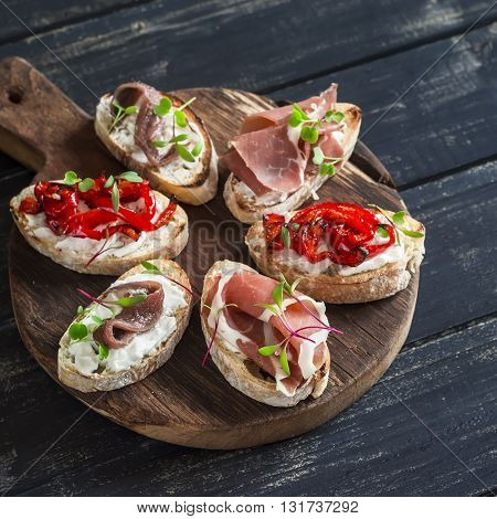 Sandwiches with goat cheese anchovies roasted peppers ham on a wooden rustic board. Delicious snack or appetizer with wine