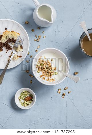 Breakfast - greek yogurt with granola and pistachios chocolate cake and coffee. On a blue stone background