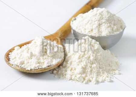 close up of soft wheat flour on wooden spoon and in metal bowl on white background