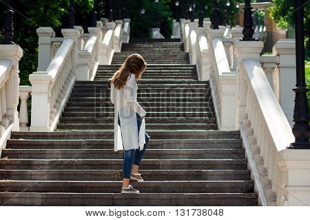 Beautiful Girl Standing With Her Back On The Stairs In The Park And Looking Down