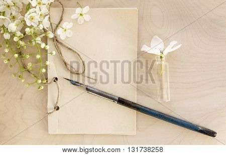 Open vintage handmade sketchbook with white bird-cherry flowers over wooden table background. Mock up retro style. Old paper notepad. Vintage retro mockup. Rough rope. Summer mock-up. Wooden background. Old pen.