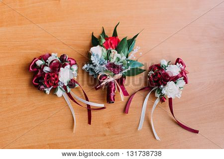 Three beautiful boutonnieres of red and white flowers on wooden rustic background.