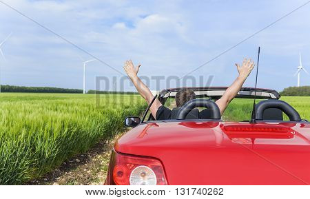 Man in a convertible car relaxes and enjoys the freedom. Travel or vacation concept.