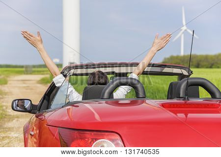 Woman in a red car in a field with wind power, raises her arms up. Travel or freedom concept.
